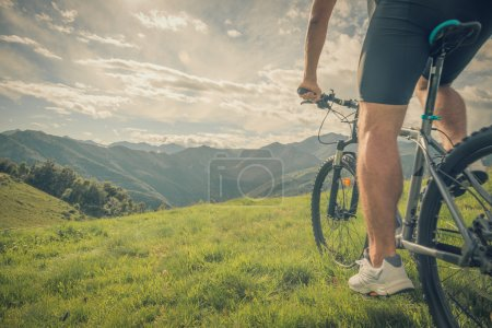 Young athletic man riding bike in sunny day in mountain