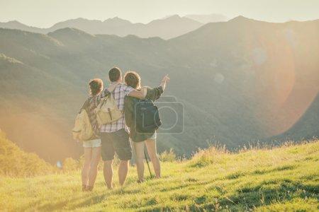 Photo pour Trois amis regardent le panorama sur la montagne - image libre de droit