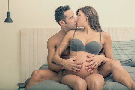 Expecting pregnant couple make cuddle in bed
