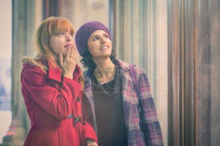 Photo pour Deux jeunes femmes regardant quelque chose avec un sentiment d'adoration, une avec la main sur la bouche - image libre de droit
