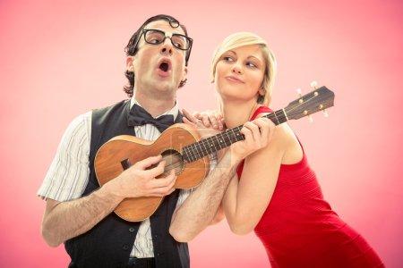 Photo pour Copain de nerd homme jouer ukulélé amour chanson pour sa petite amie pour la Saint-Valentin - image libre de droit