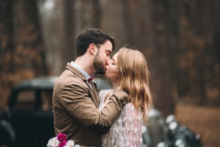 Romantic fairytale wedding couple kissing and embracing in pine forest near retro car.