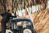 Elegantní Svatební pár, nevěsta, ženich, líbání a objímání poblíž retro auto na podzim