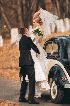 Photo pour Couple élégant mariage, mariée et le marié baisers et des caresses près de voiture rétro en automne - image libre de droit