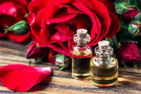 Essential oil in glass bottle with red rose flowers and petals on wooden background. Beauty treatment. Spa and aromatherapy concept. Selective focus.