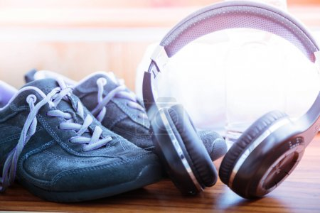 Sport concept.  Healthy lifestyle. Grey sport  shoes and headphones for jogging and sports. Sports equipment.