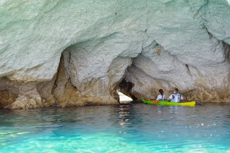 People with kayaks exploring the caves, Melos, Greece