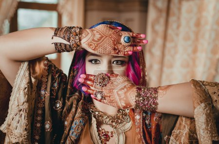 portrait of a beautiful young woman in traditional Indian ethnic dress and painted ational patterns on the hands, mehendi