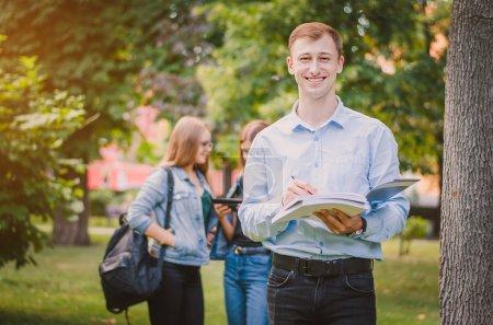 Photo pour Heureux étudiant garçon souriant à bretelles, chemise et pantalon avec un livre dans le parc de l'été, derrière elle, il y a des filles et communiquer - image libre de droit