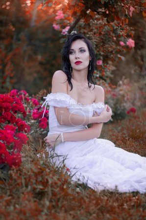 Beautiful young brunette woman in a long white dress sitting in the bushes in the garden with roses. Bride