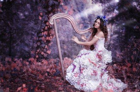 Photo pour Belle femme aux cheveux bruns avec une couronne de fleurs sur la tête, portant une robe blanche jouant de la harpe dans la forêt - image libre de droit