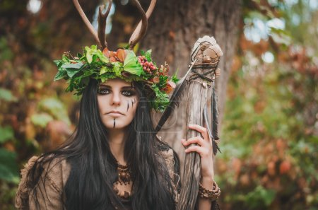portrait of a beautiful brunette in the form of shaman, with floral wreath on her head and horns