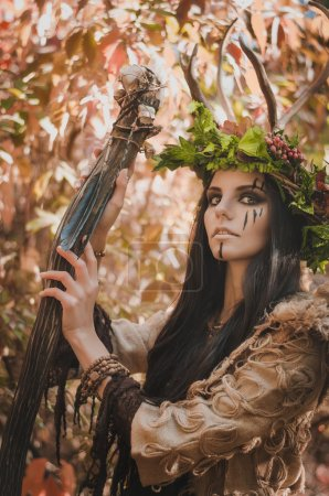 Portrait of a brunette with a painted face in the image of shaman and floral wreath on her head and horns