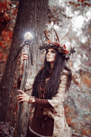 beautiful brunette with painted face, clothes shaman, a floral wreath on her head and horns, holding a glowing wooden staff, in the woods