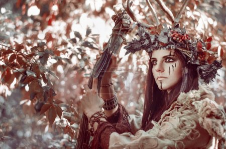 portrait of a beautiful brunette with a painted face, a floral wreath on her head and horns in the form of shaman, with the village staff in hand
