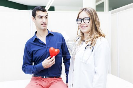 female doctor listens to the heartbeat of a patient