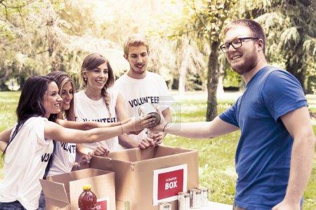 Photo pour Groupe de bénévoles reçoit un don de nourriture - image libre de droit