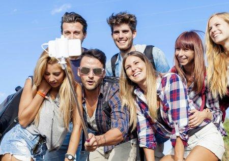 Photo pour Groupe d'amis prenant un autoportrait avec selfie stick - image libre de droit