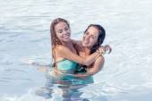 Pretty girls play and hug in pool
