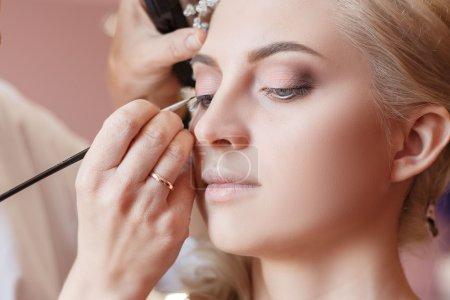 Make-up artist doing makeup for photos