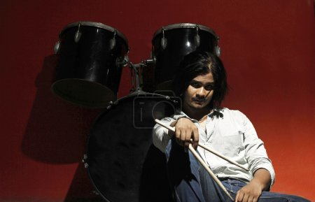 Young drummer holding sticks and sitting next to drum kit