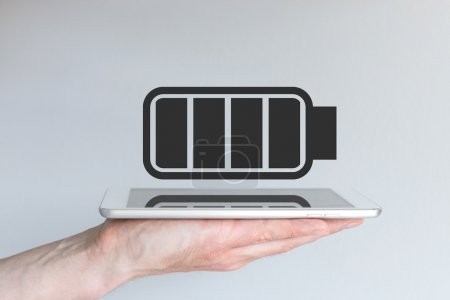 Photo for Concept of battery life for mobile devices. Hand holding modern smart phone or tablet. - Royalty Free Image