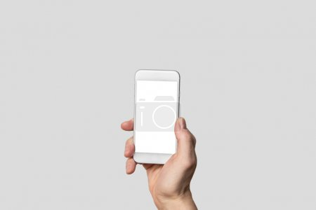Hand holding modern smartphone in front of isolated background and blank touch screen