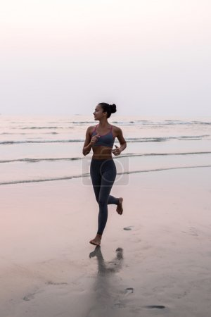 Young slim woman running barefoot on the ocean beach at sunset