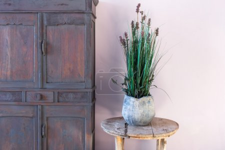 Old vase with flowers on vintage round wooden table