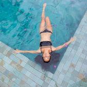 Beautiful sexy woman enjoying in luxury swimming pool in black swimsuit