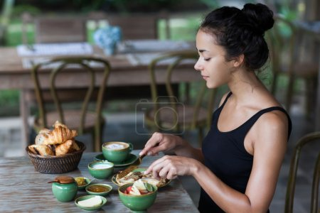 Young woman having breakfast and cut pancakes with golden fork and knife