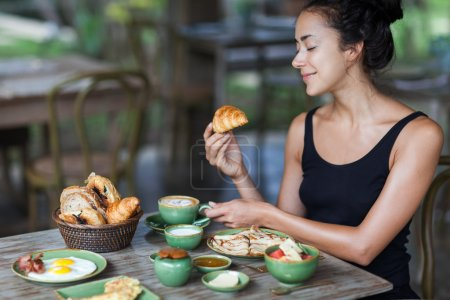 Young woman enjoying breakfast and holding croissant in hand. Morning good mood