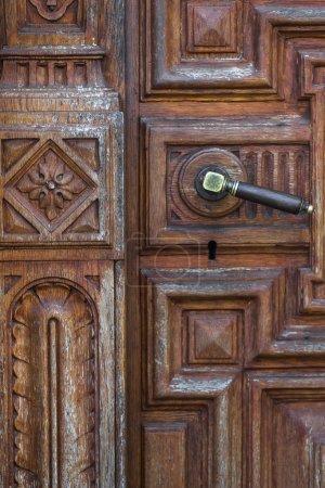 Vintage bronze door knob on handmade wood carving door