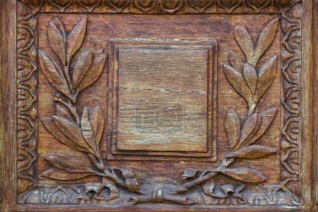 Wood carving door with empty plate with laurel branch ornament