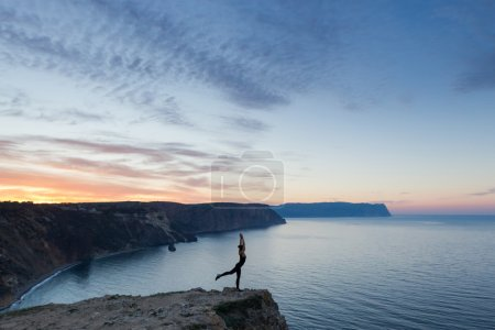 Woman practicing yoga near sea