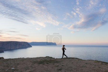 Photo pour Jeune femme courant le matin le long de la côte - image libre de droit