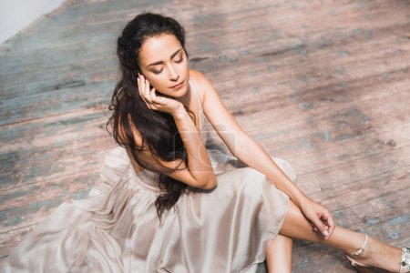 Photo for Beautiful girl with long hair sitting on the wooden floor - Royalty Free Image