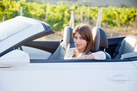 Photo for The girl sitting behind the wheel of a white sports convertible - Royalty Free Image