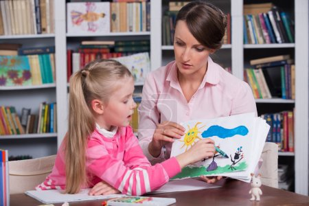 Photo for Child psychologist with a sad little girl, the doctor looks at the childs picture - Royalty Free Image