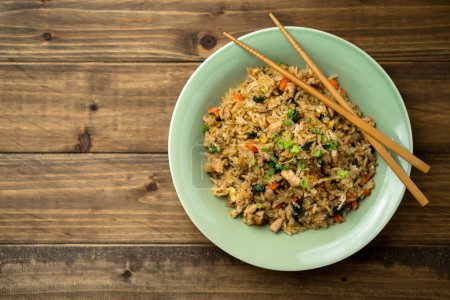 Photo for Basil chicken fried rice with chopsticks on a wooden background viewed from above. This thai inspired meal is perfect for a quick lunch or served as side dish. - Royalty Free Image