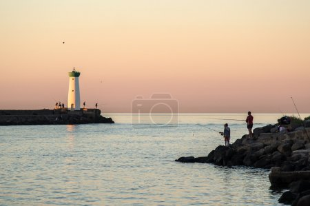 Fishermen at dawn with the lighthouse