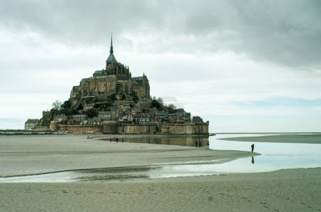Photo for Mont Saint-Michel island in France and tourists on sand - Royalty Free Image