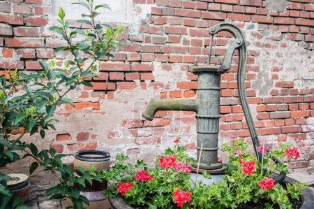 Photo pour Pompe manuelle bien (pipe à eau vintage) dans un jardin, Hunspach, Alsace, France - image libre de droit
