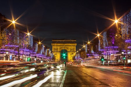Photo for Evening traffic on Champs-Elysees in front of Arc de Triomphe (Paris, France) at Christmas Time - Royalty Free Image