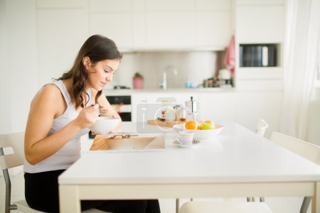 Young brunette is reading the newspaper while having breakfast at home.Modern woman lifestyle-healthy fitness breakfast,coffee and fruit,reading motivational quotes