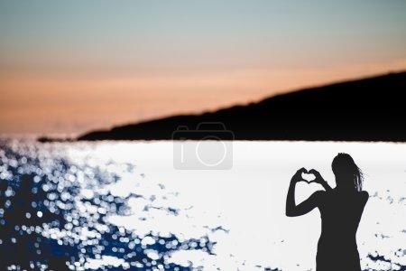 Photo pour Femme heureuse libre profitant du coucher du soleil.. Faire place à l'éclat doré du soleil couchant, profiter de la paix, la sérénité dans la nature.Vitalité des vacances concept de vie saine.Silhouette main dans la forme du cœur - image libre de droit