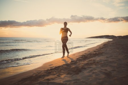 Runner woman jogging on beach in sports bra top.Beautiful fit female fitness woman training and working out outside in summer as part of healthy lifestyle