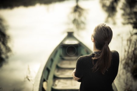 Photo for Girl at the old fishing boat looking to the lake.Melancholia sadness sorrow concept. - Royalty Free Image