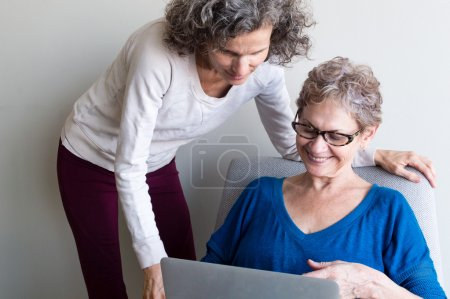 Middle aged daughter with older mother and computer