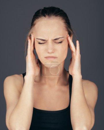 Woman having headache on gray background